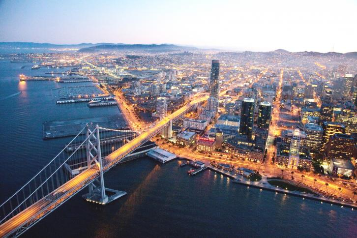 Aerial photo of West Span of Bay Bridge and lighted streets of San Francisco