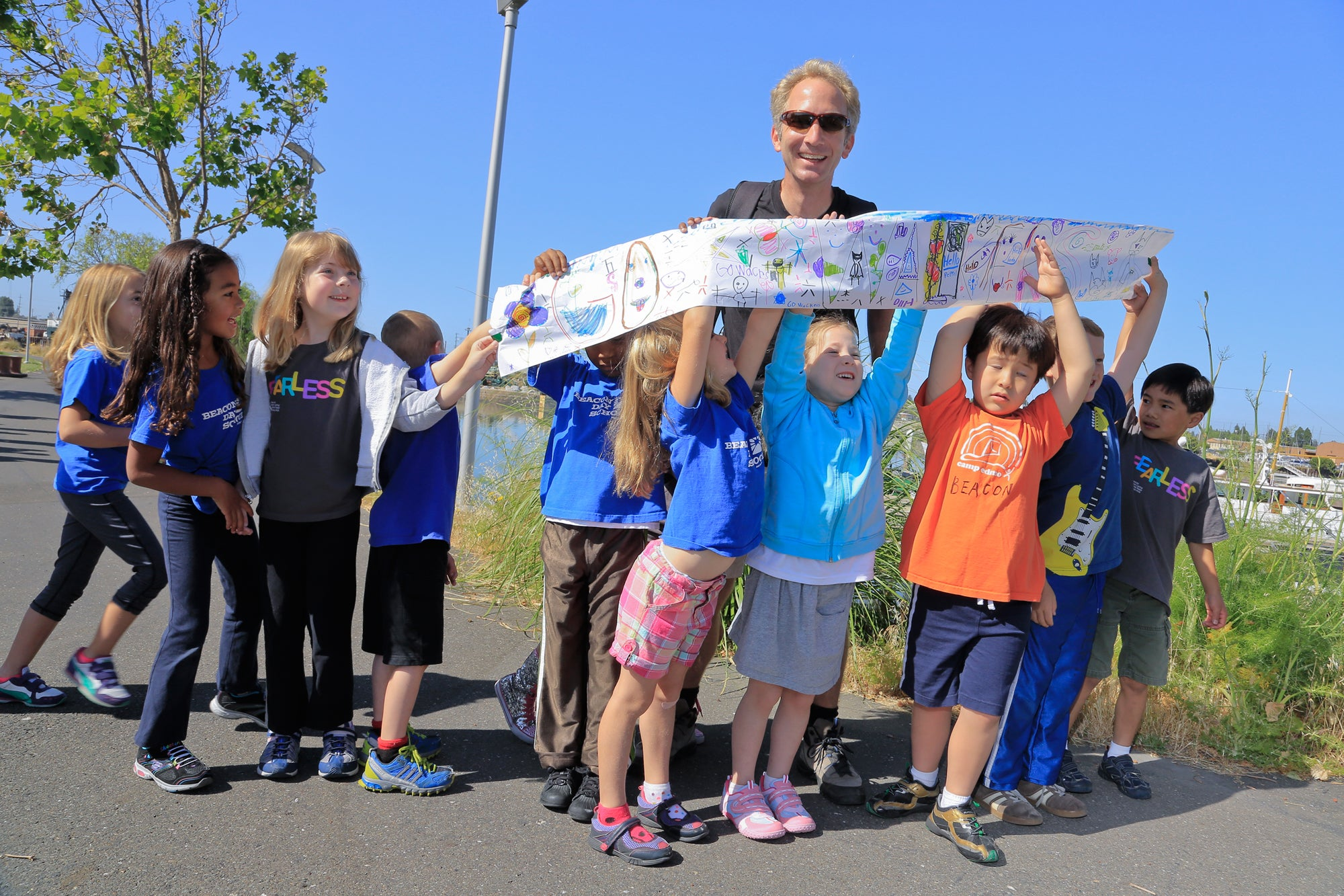 Beacon Day School students proudly display their artwork in support of the Bay Trail; Kurt Schwabe pauses for a photo op with the kids before resuming his 30-day trek around the San Francisco Bay.