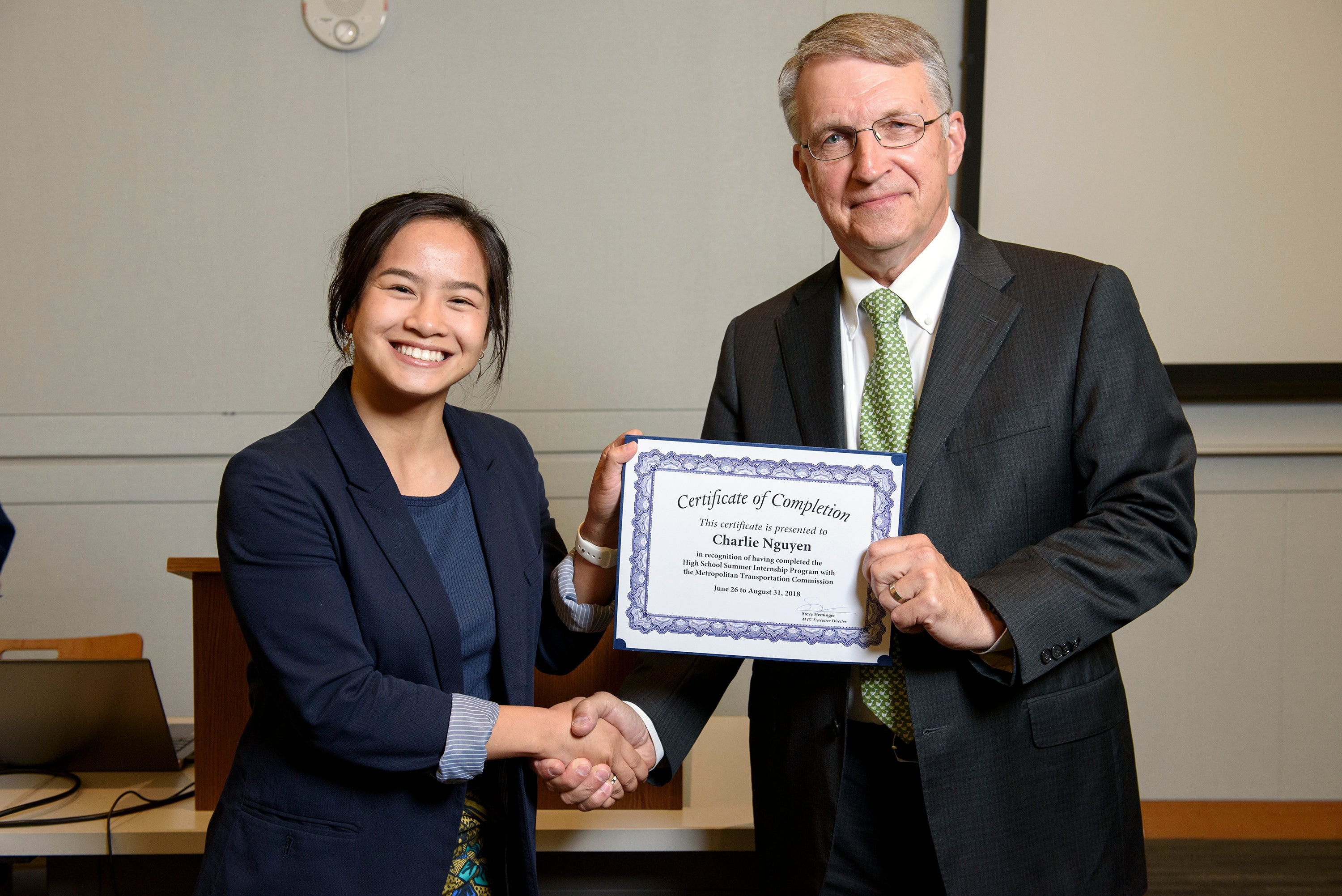 MTC high school intern Charlie Nguyen receives her certificate for completing the program.