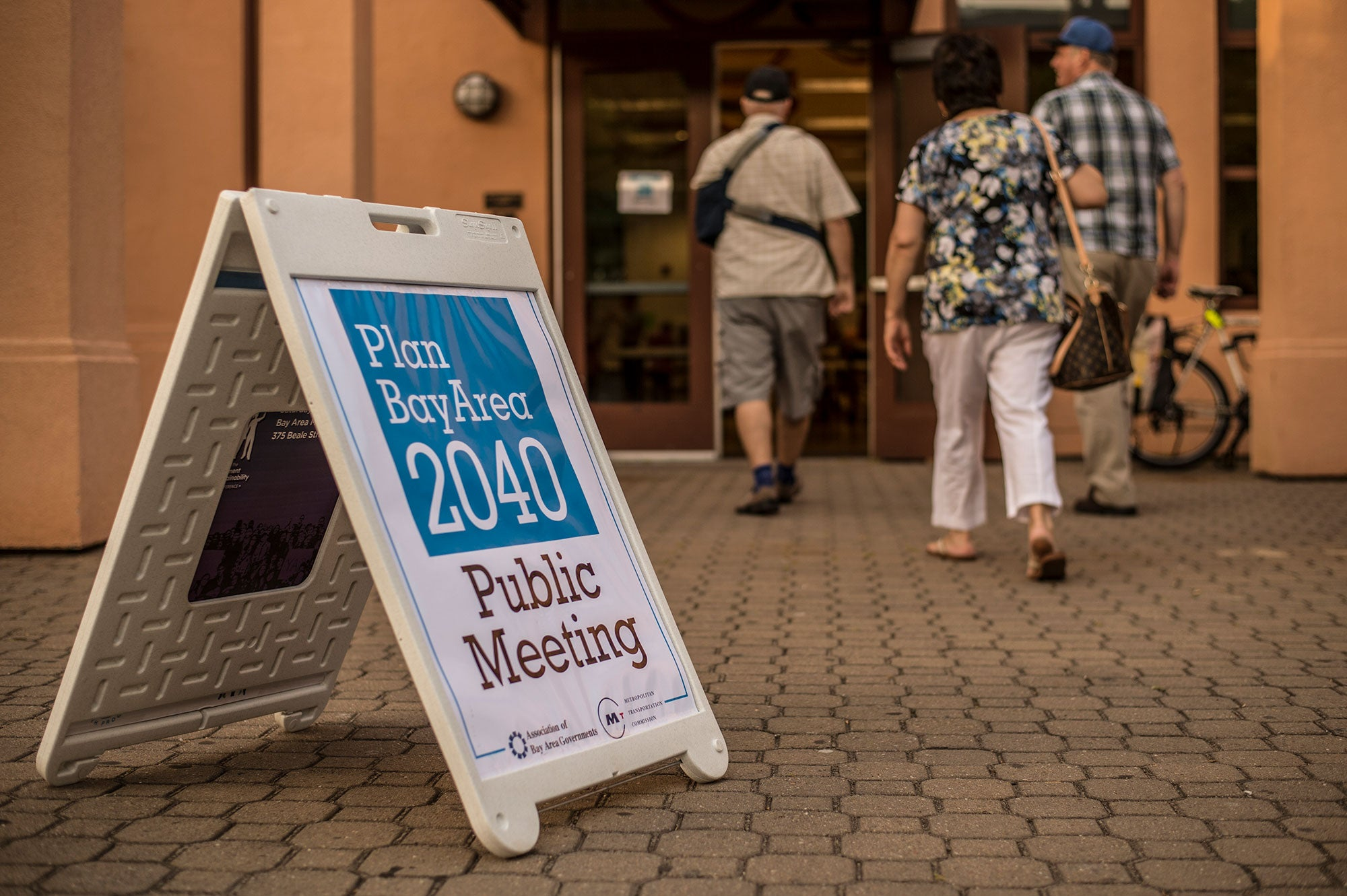 In the foreground a sandwich board advertising the Plan Bay Area 2040 public meeting is displayed, with three adults walking into the building in the background.