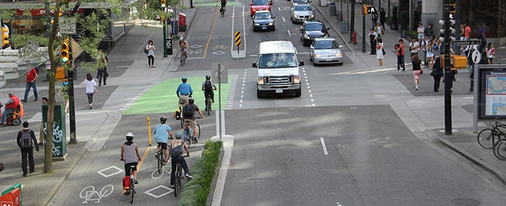 Cyclists use a separated bike lane on a busy street with cars and pedestrians nearby