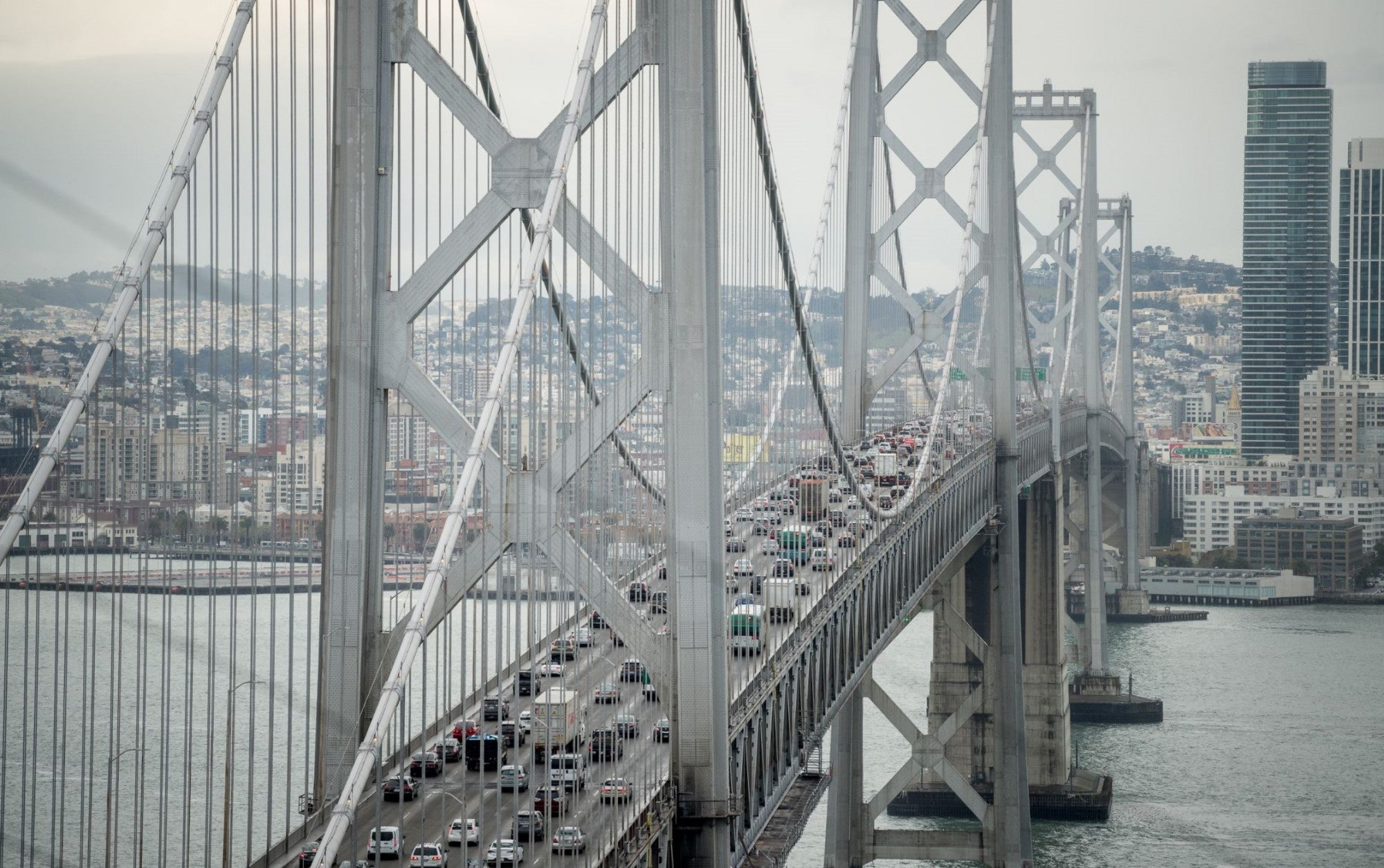 Cars travel west toward San Francisco on the upper deck of the Bay Bridge while SF's cityscape is in the background