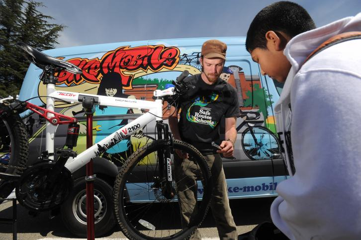 A BikeMobile team member helps a boy fix his bike.