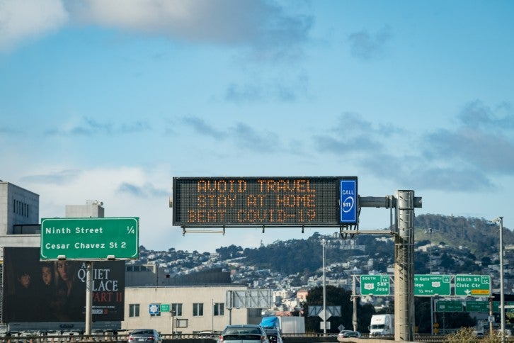 "Motorists travel on southbound U.S. 101 in San Francisco, with a sign for Ninth Street and Cesar Chavez Street on the left and a changeable message sign in the center that reads ""Avoid travel stay at home beat COVID-19"""
