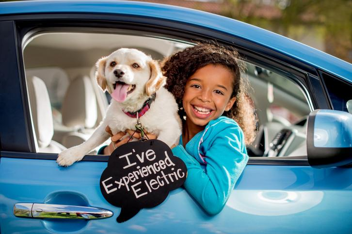 "A girl and dog sit in an electric vehicle at an ""Experience Electric"" event San Jose."