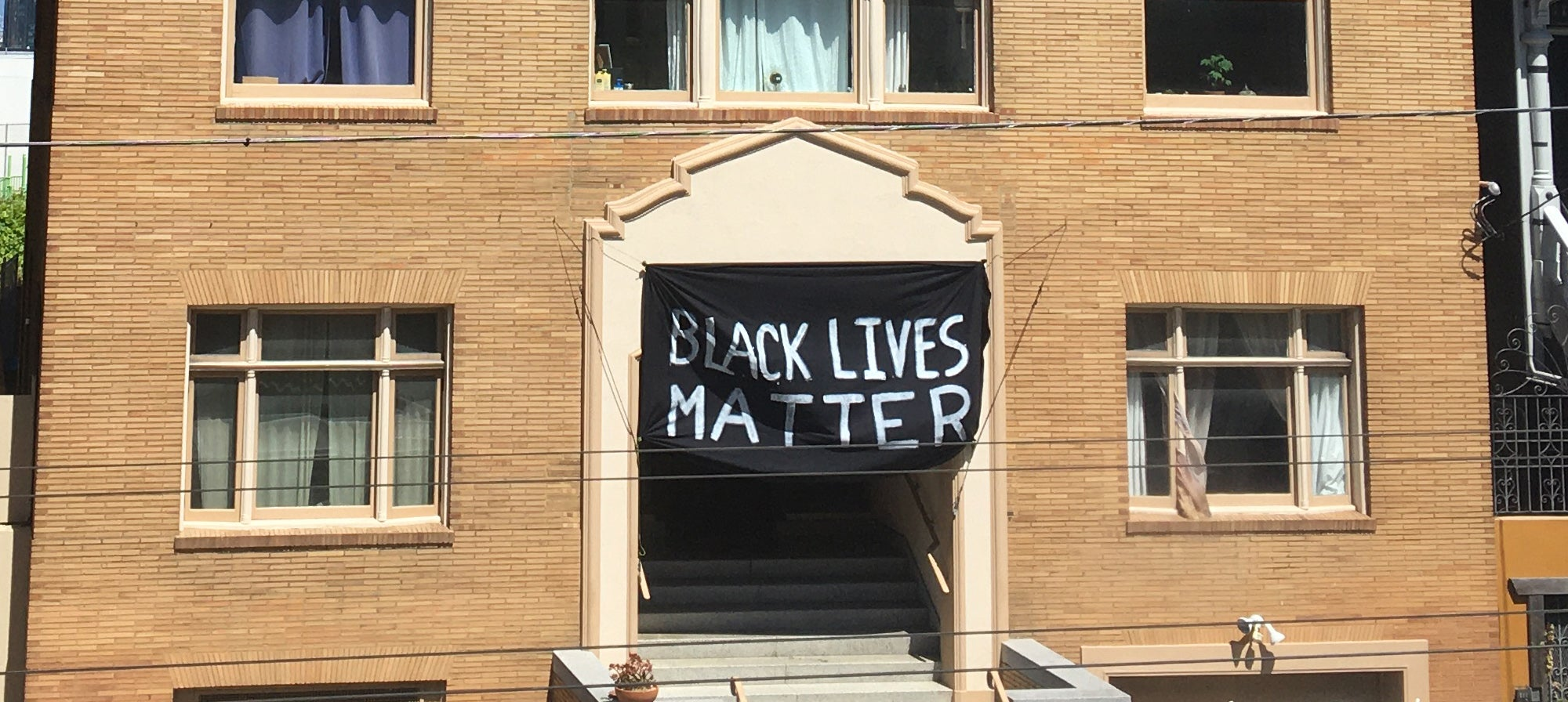 A Black Lives Matter banner hangs on the front of a brick building
