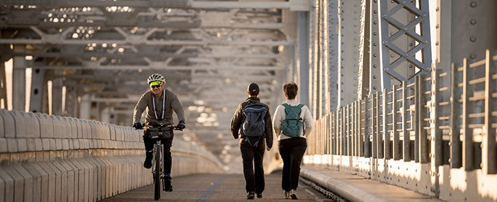 A cyclist and pedestrians on the Richmond-San Rafael bicycle/pedestrian path