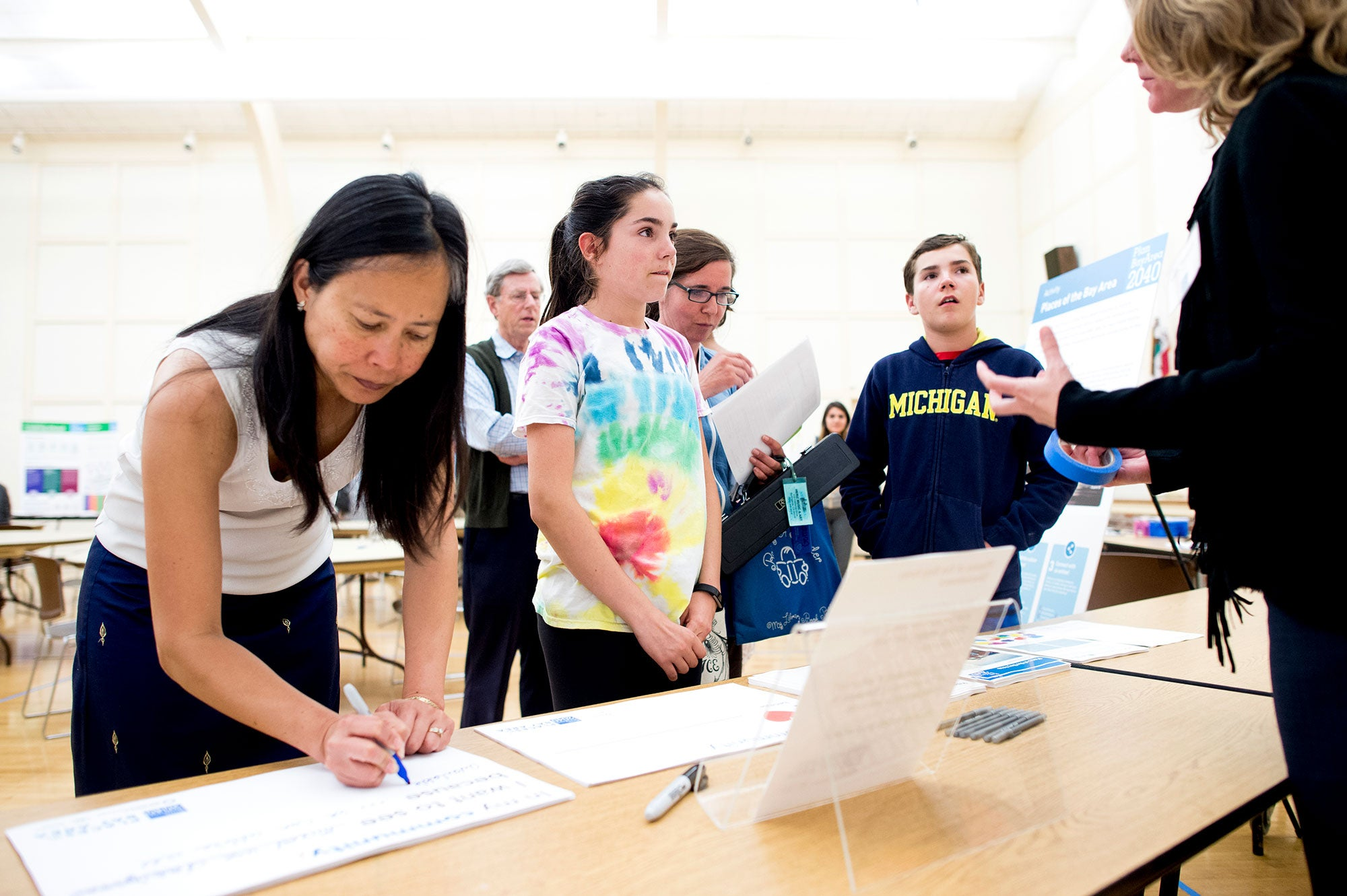 A woman fills out a comment form while children discuss Plan Bay Area 2040 with staff at the Spring 2016 San Mateo County open house in Burlingame.