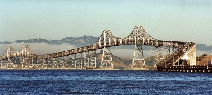 Richmond-San Rafael Bridge with fog in the background and sapphire-blue water below.