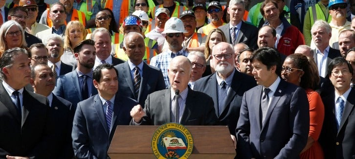 Calif., Gov. Jerry Brown, center, discusses a plan to raise $52 billion to fix California roads, during a news conference Wednesday, March 29, 2017, in Sacramento, Calif. (AP Photo/Rich Pedroncelli)
