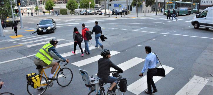 An intersection busy with pedestrians, cyclists and cars