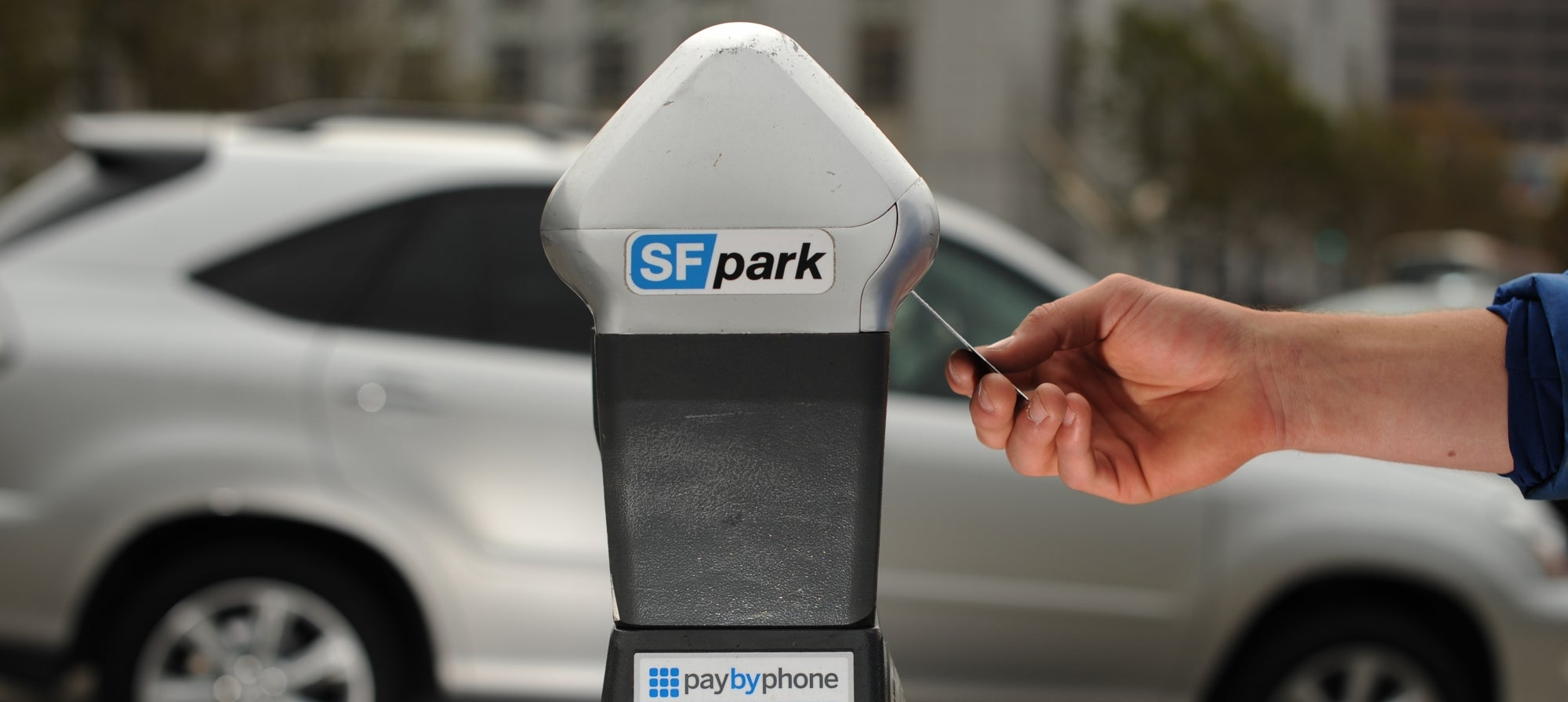 A driver inserts a credit card in a smart parking meter in SF.
