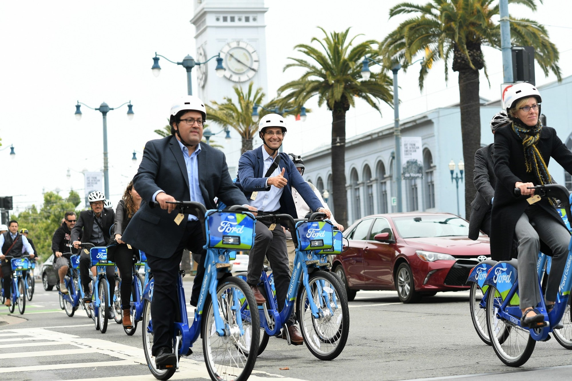 Individuals riding Ford GoBikes in front of the San Francisco Ferry Building.