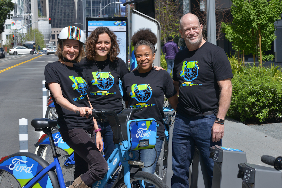 MTC staffers model this year's Bike to Work Day T-Shirt, at the Ford GoBike Station adjacent to MTC's offices at the Bay Area Metro Center in San Francisco.
