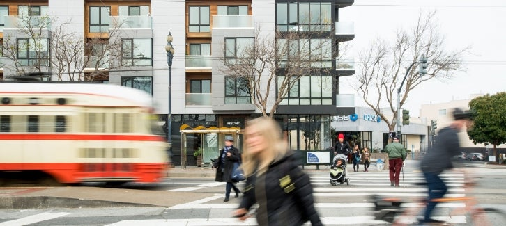 Pedestrians, bicyclists and a cable car all share the street space on Market Street.
