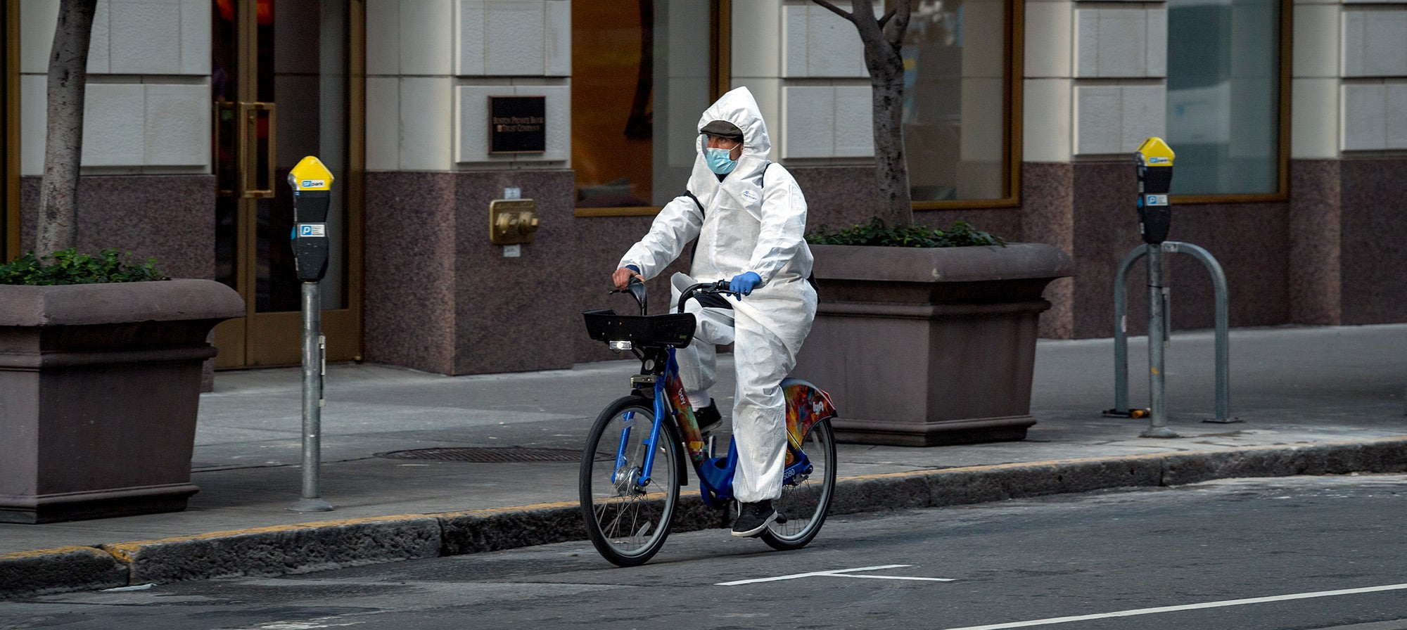 Covid-19 Crisis: A man wearing a protective suit while cycling