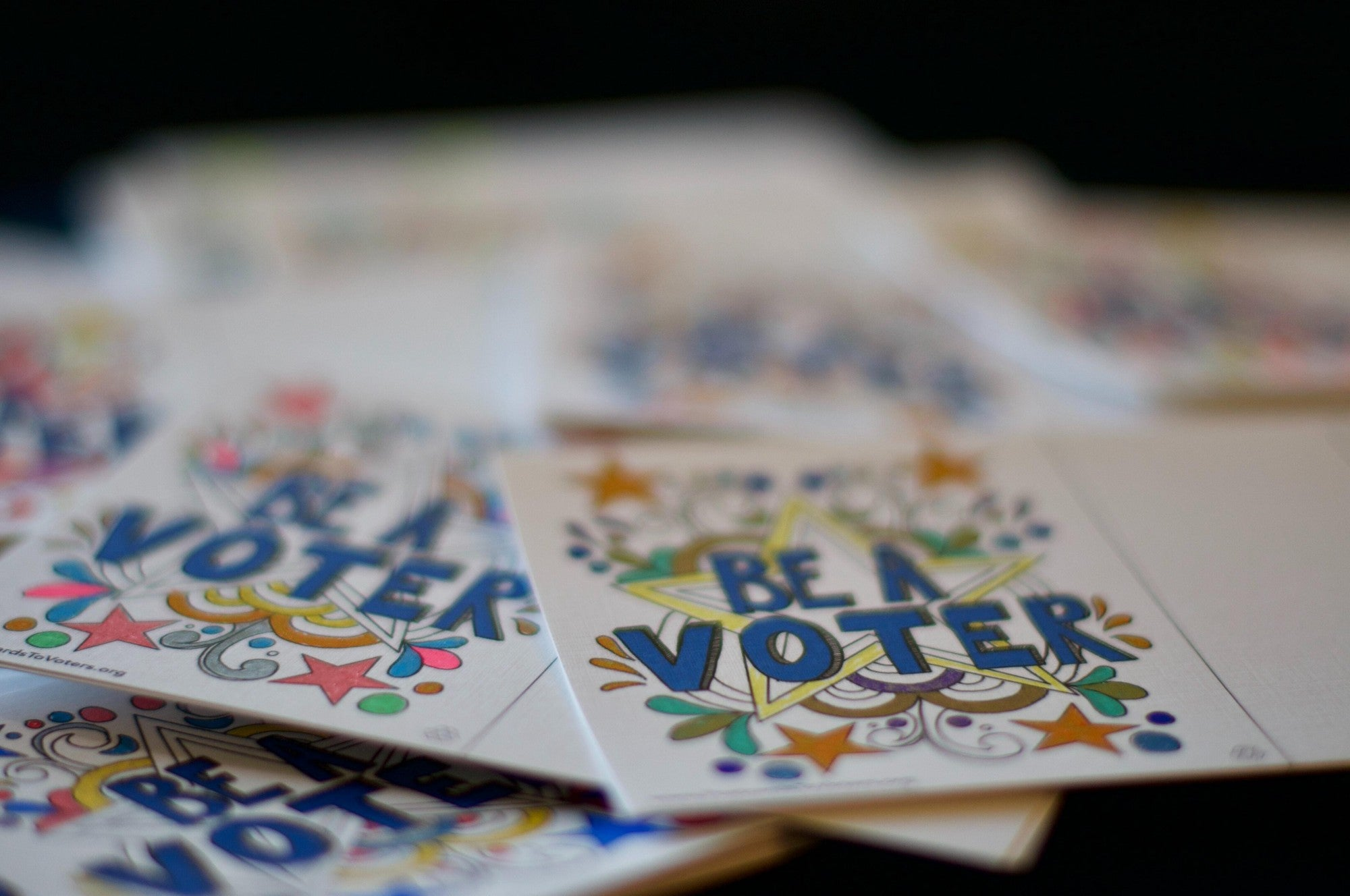 "A stack of postcards with illustrations and ""Be a voter"" message"