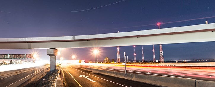 Highway and overpass at night with an arrow on the roadway in the foreground