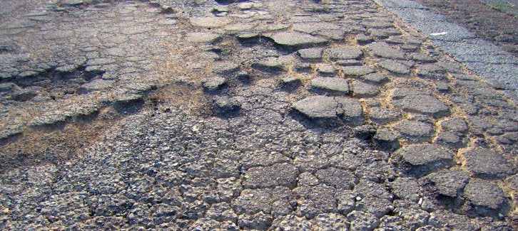 Image shows failed pavement, marked by potholes and alligator cracking