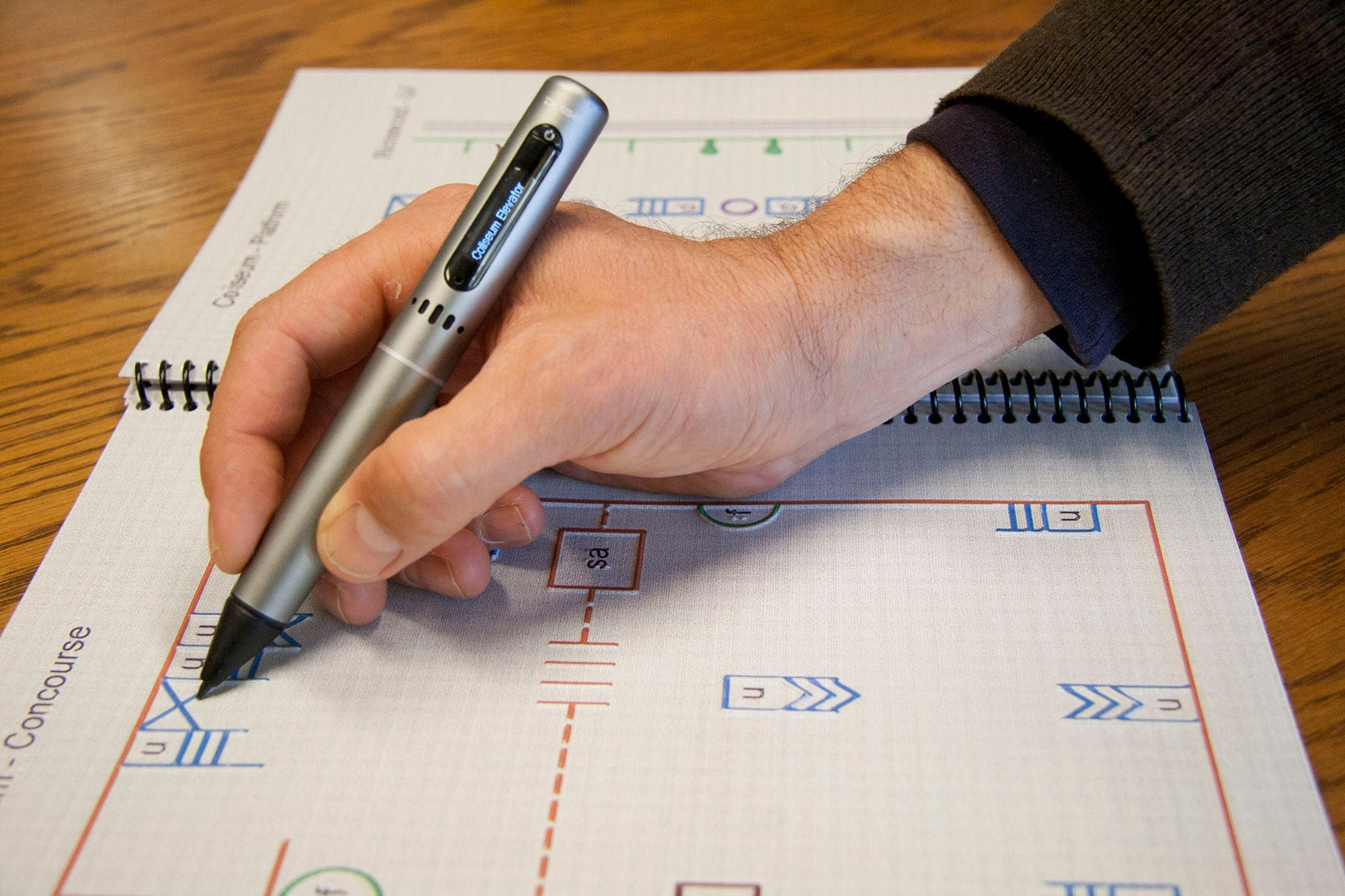 "A hand holds a specially designed pen to ""read' a tactile map"