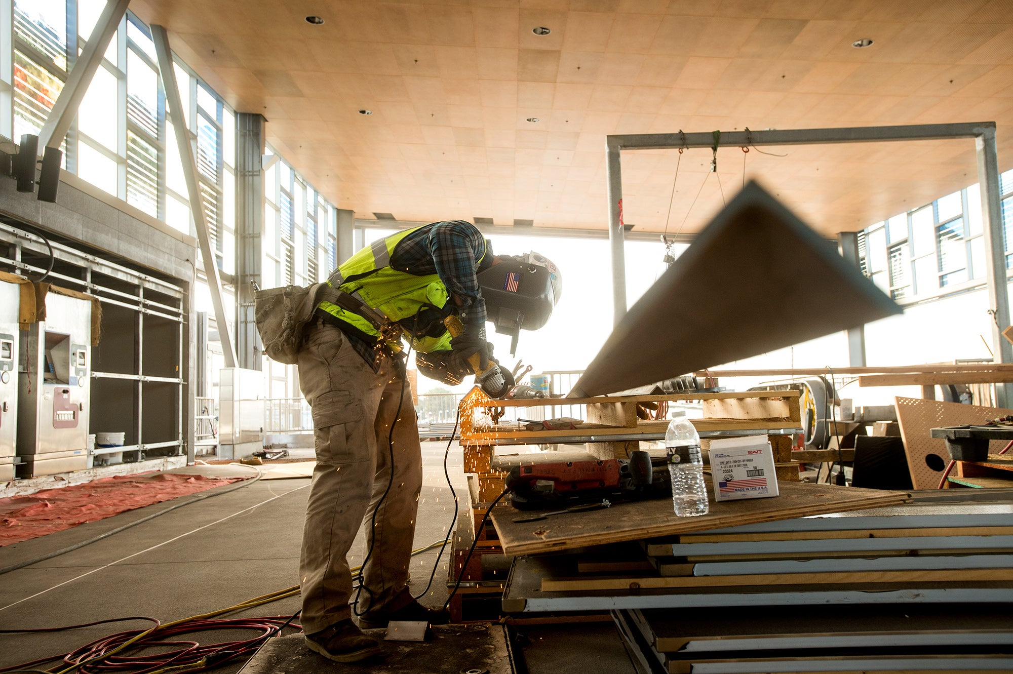 Warm Springs BART Station: Worker cuts stainless steel to make the framing for ticket machines.