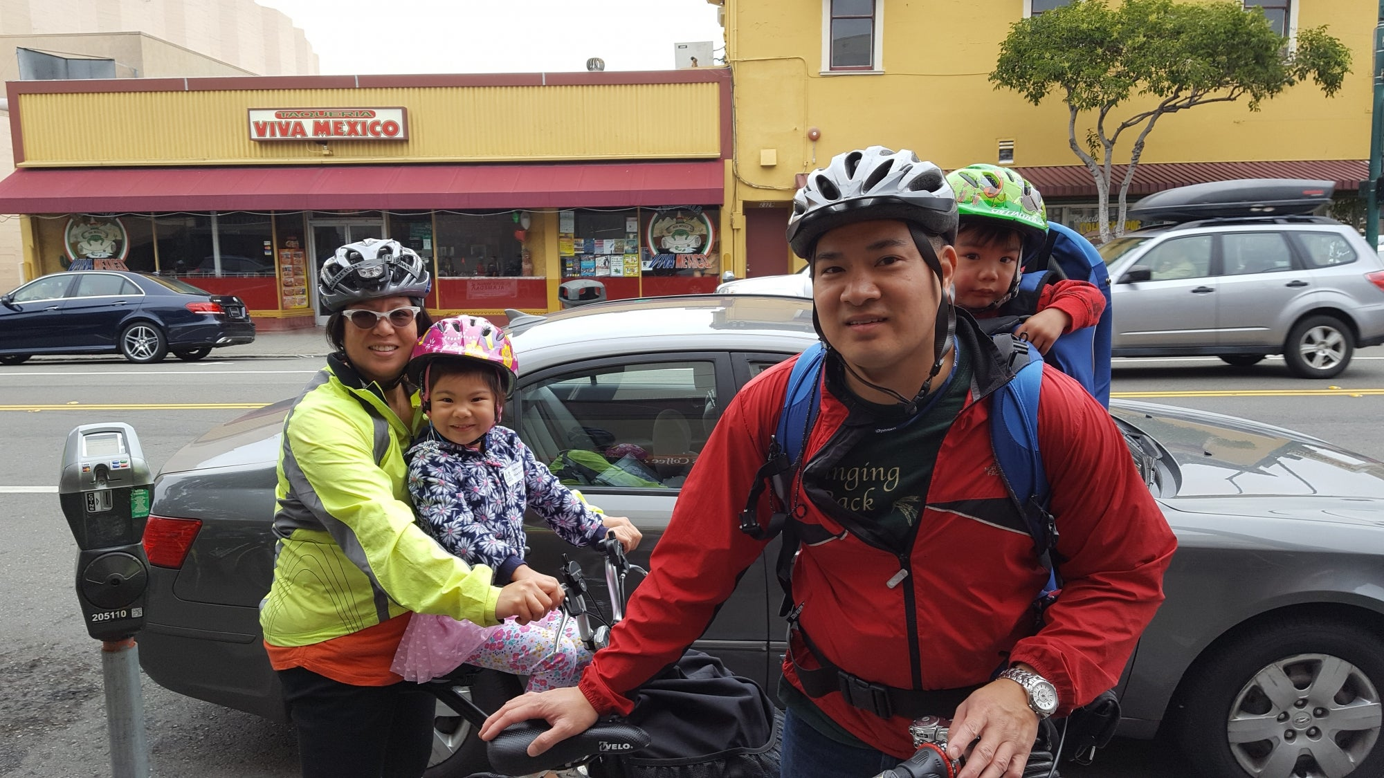 A family of bicyclists--two parents and two children--smile for the camera