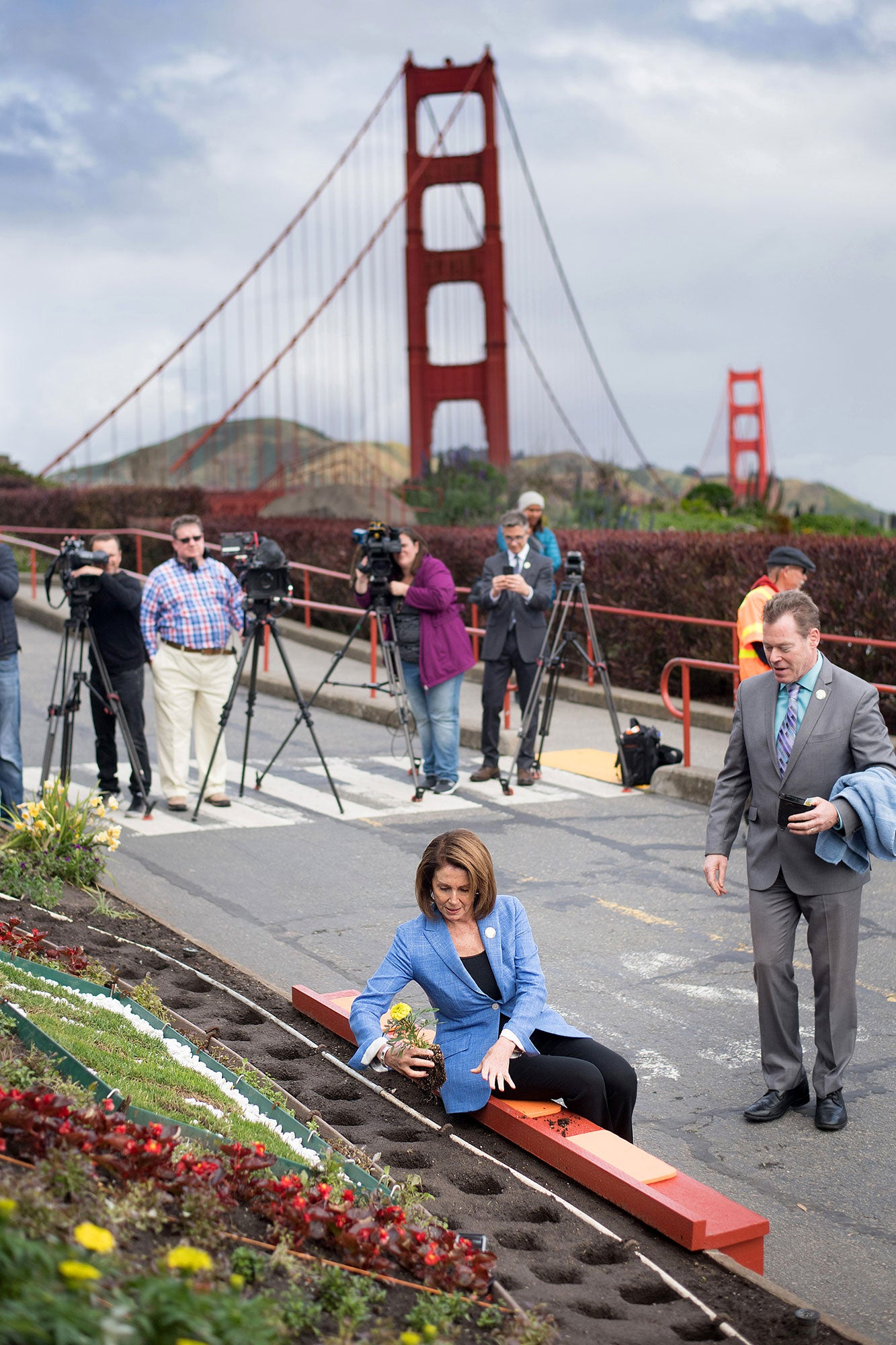 Image of Nancy Pelosi planting a plant in a commemorative garden.