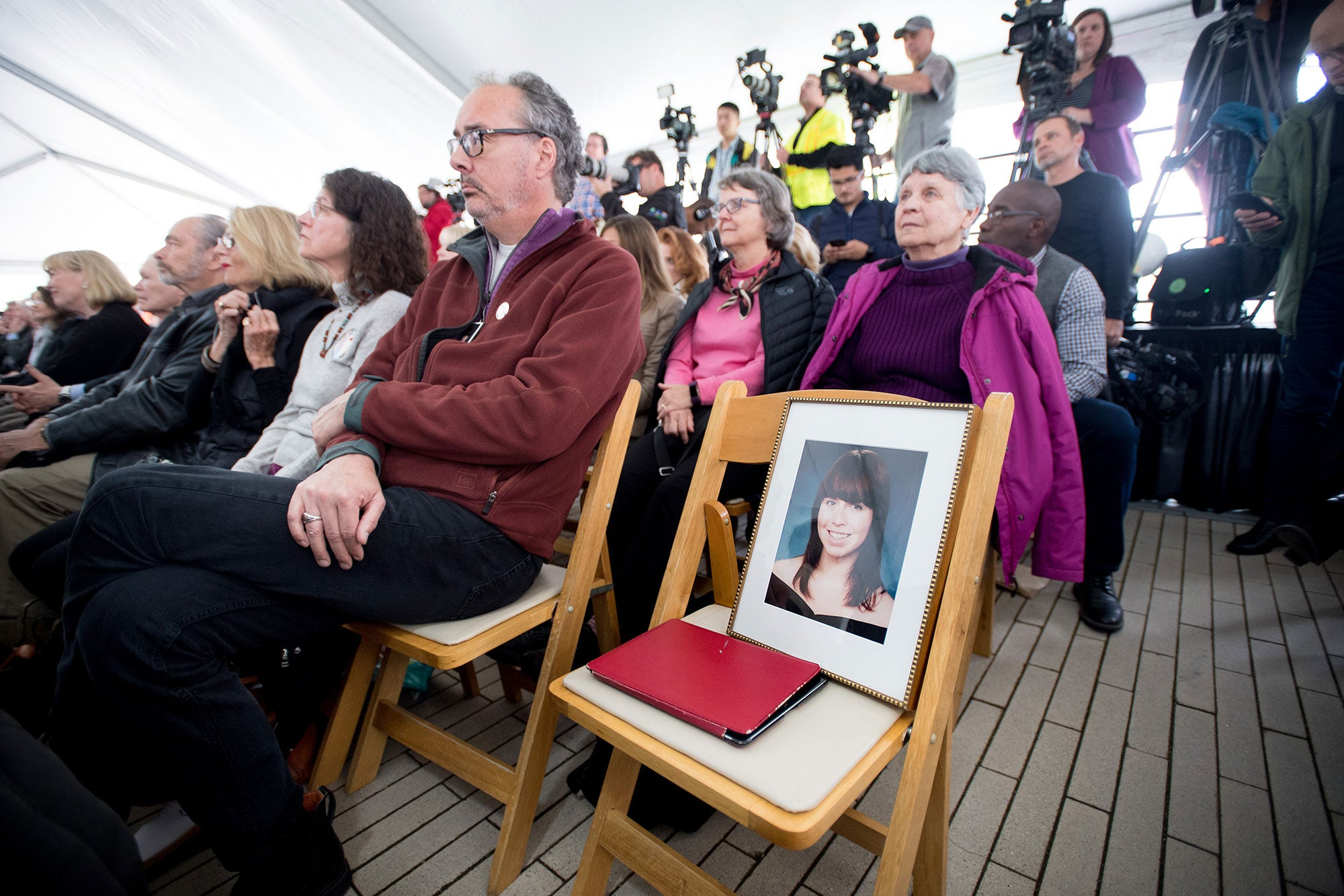 family member sits with portrait of loved one who committed suicide.