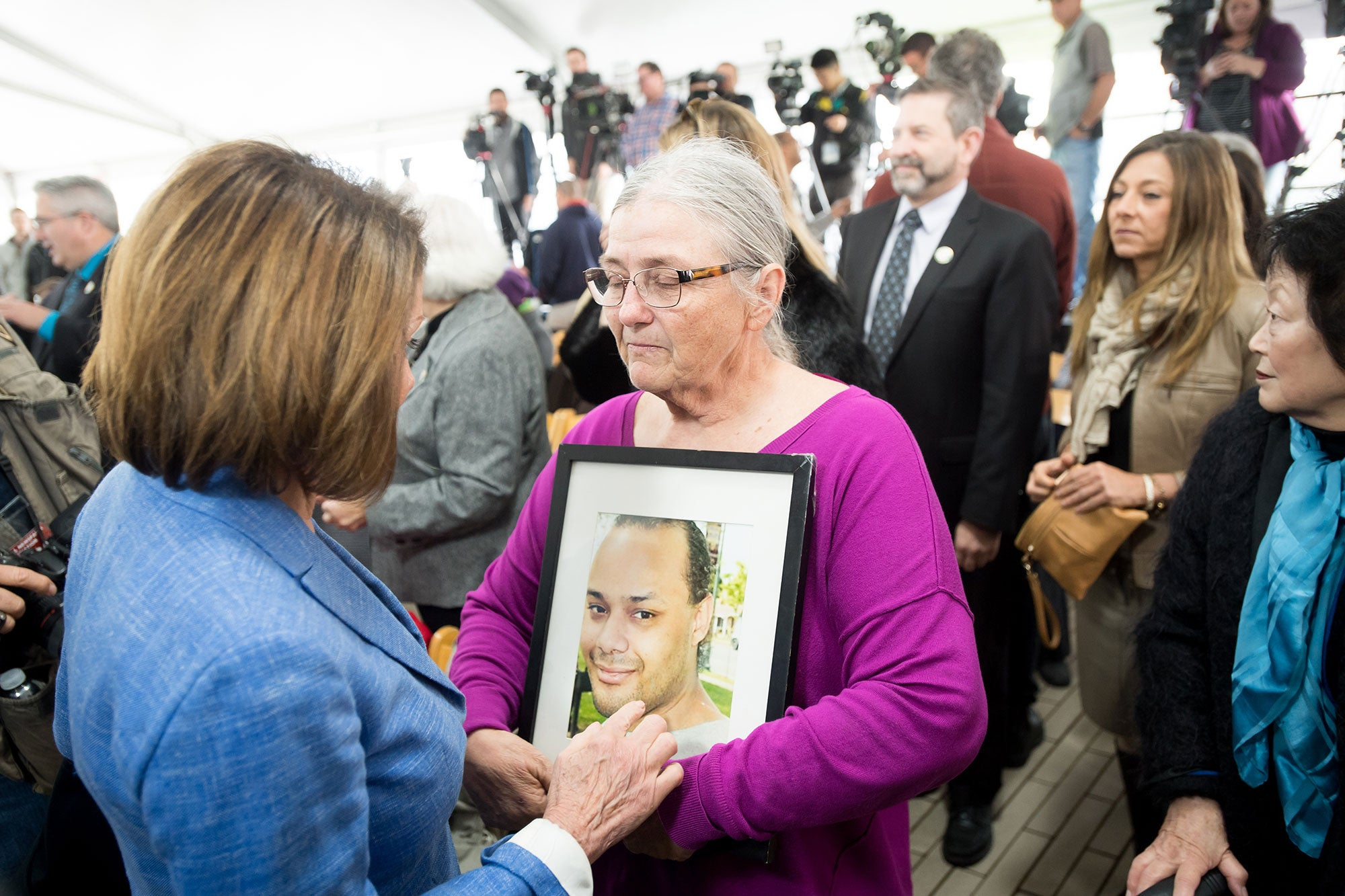 Nancy Pelosi with a grieving family member.