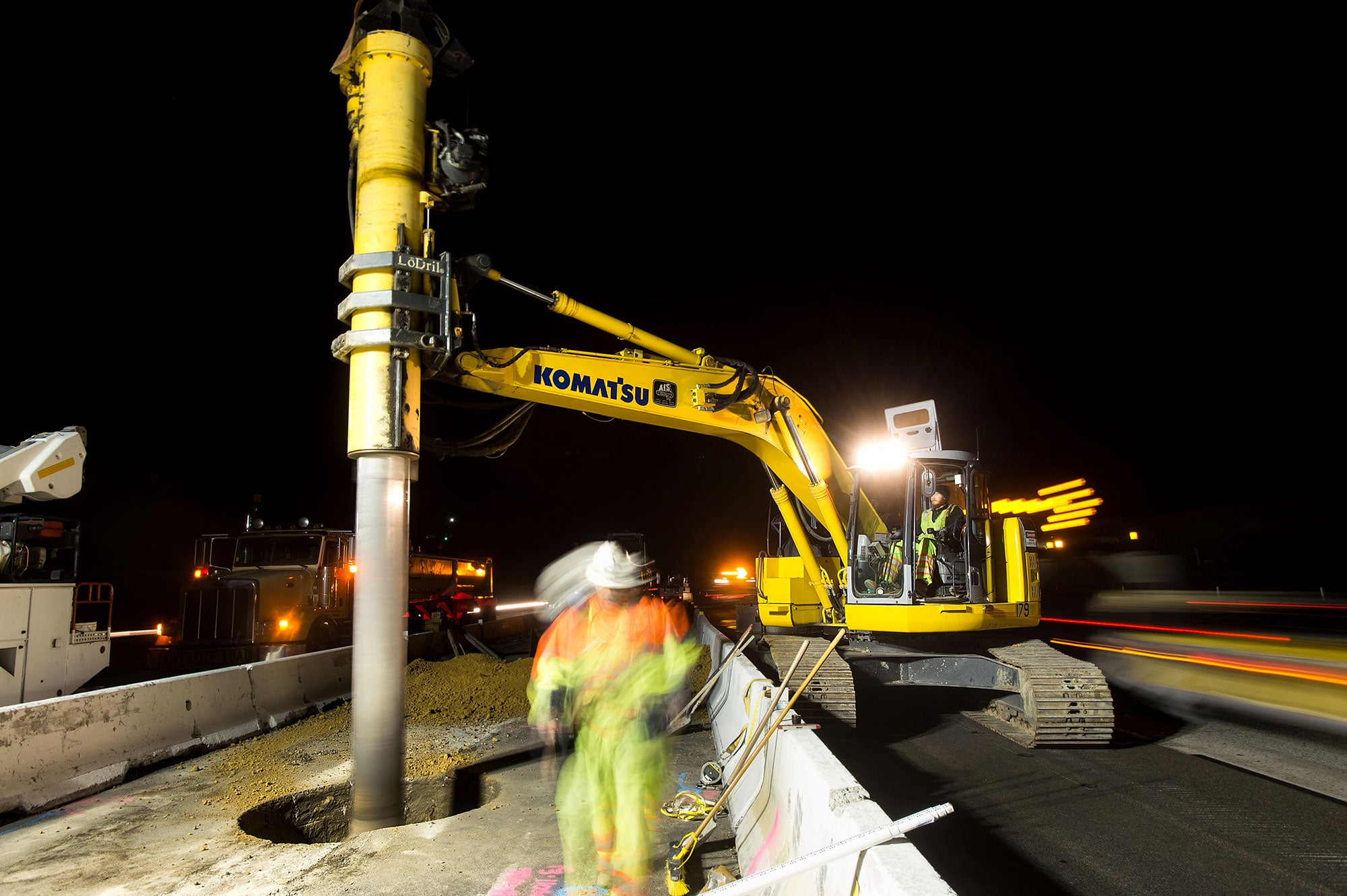 Construction crews use an excavator in pre-drilling activities for express lane sign foundations.