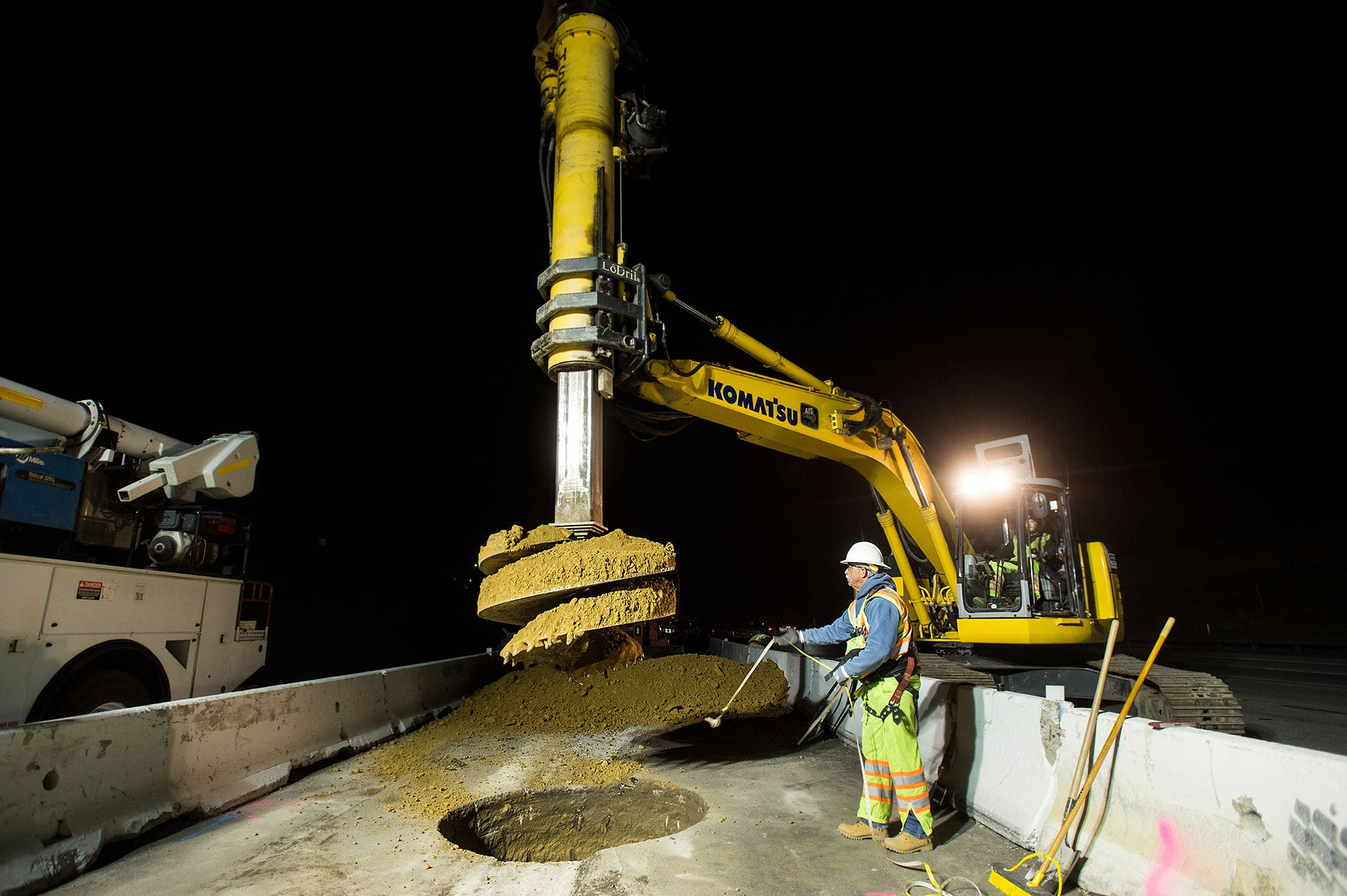 An excavator with a drill attachment pre-drills a shaft where metal rebar cages and concrete will be placed.