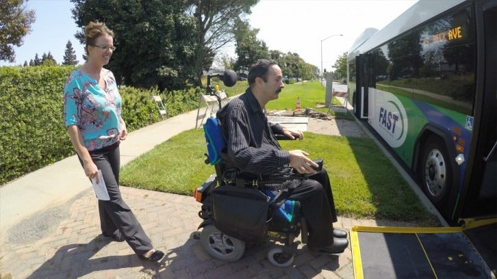 A man in a wheelchair boards a bus using the bus's lift, while a woman walks behind him.