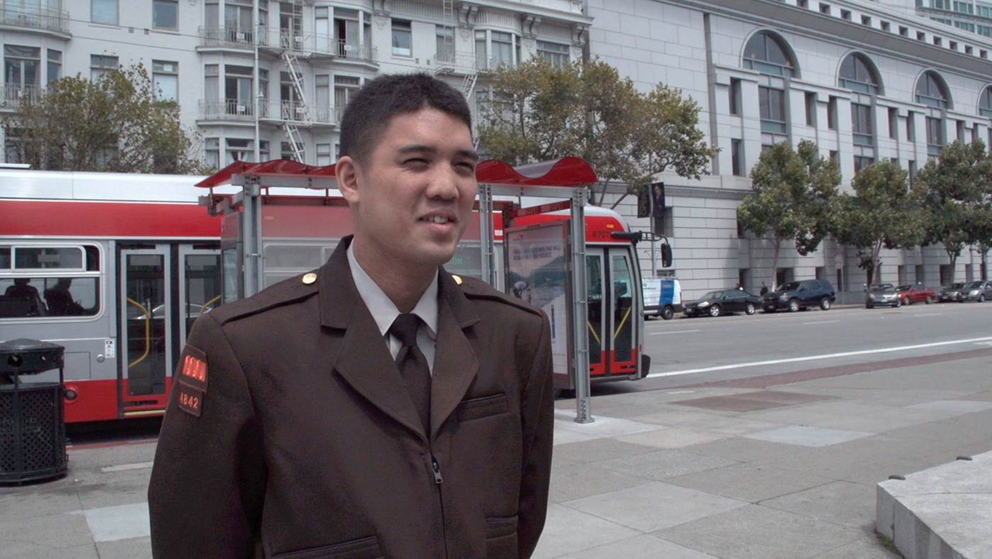 Jose Macasocol stands in uniform in San Francisco's Civic Center, with a Muni bus parked at a bus stop.