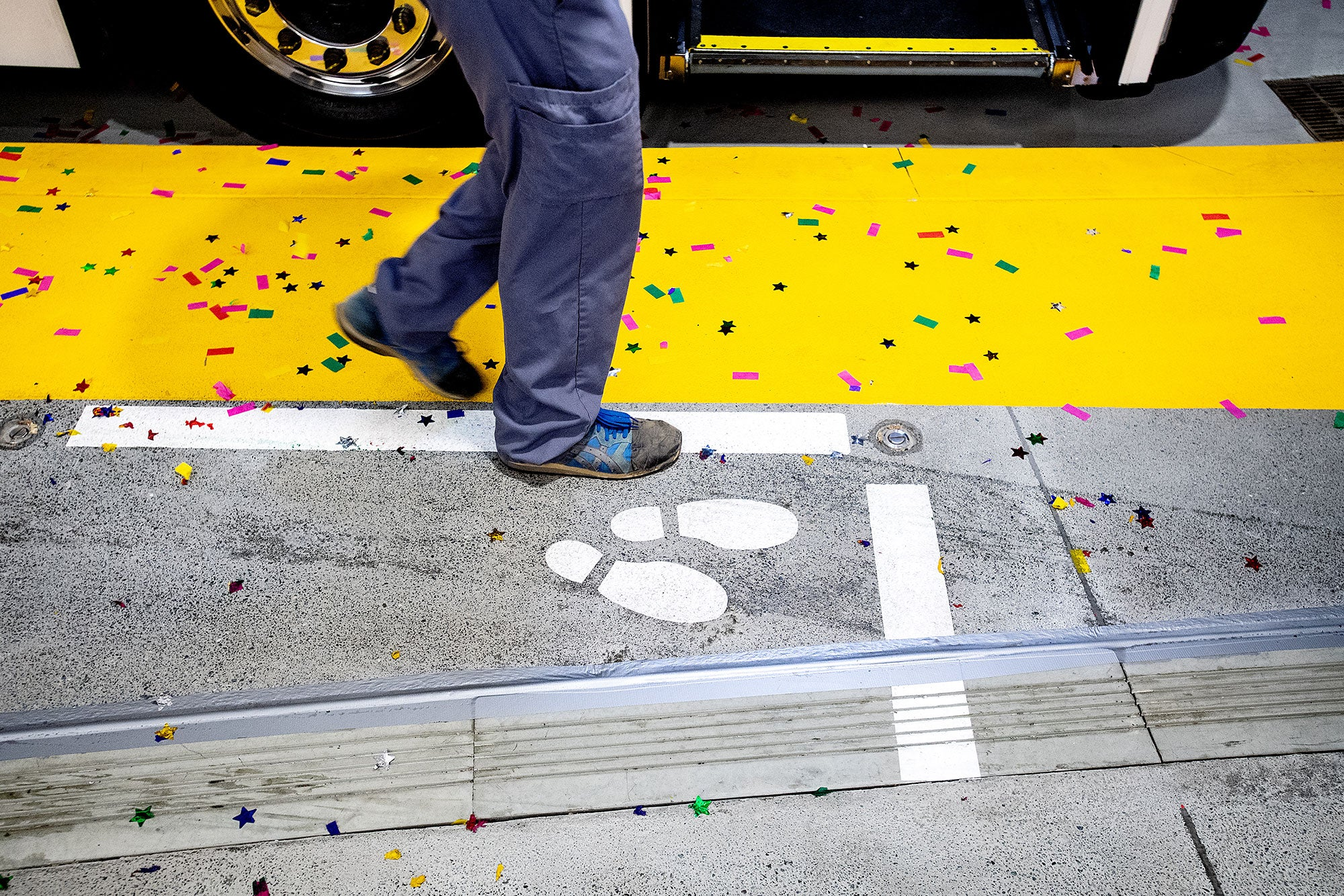 Confetti covers a platform as the first regular service AC Transit bus arrives at the Salesforce Transit Center