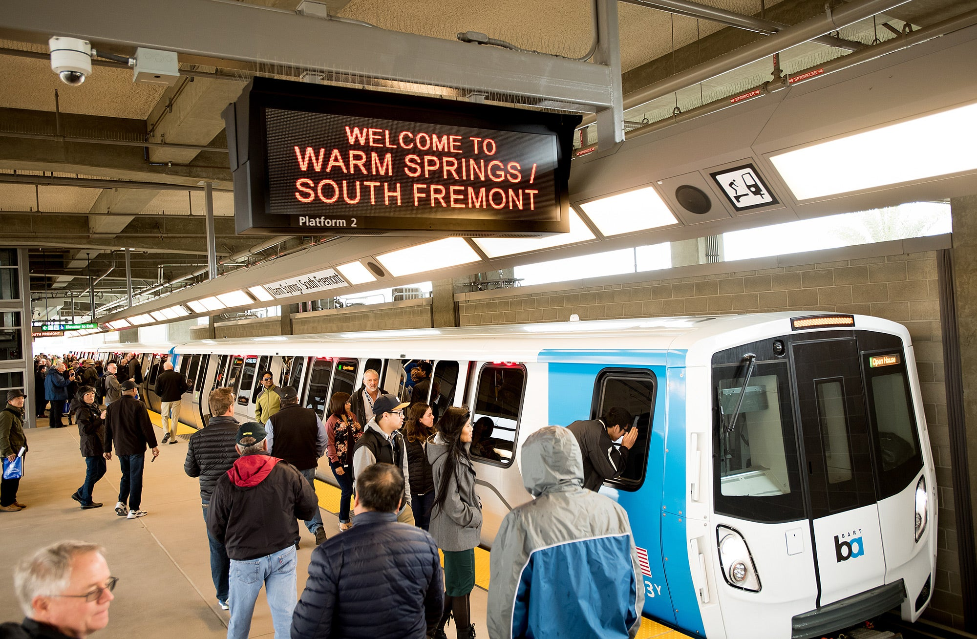 """Riders on the platform, with """"Welcome to the Warm Springs/South Fremont"""" message in the timetable sign above the BART train."""