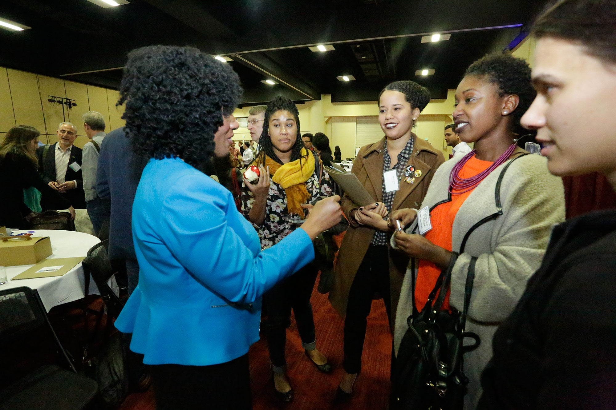 Economist Nela Richardson speaks with a group of forum attendees after her presentation.