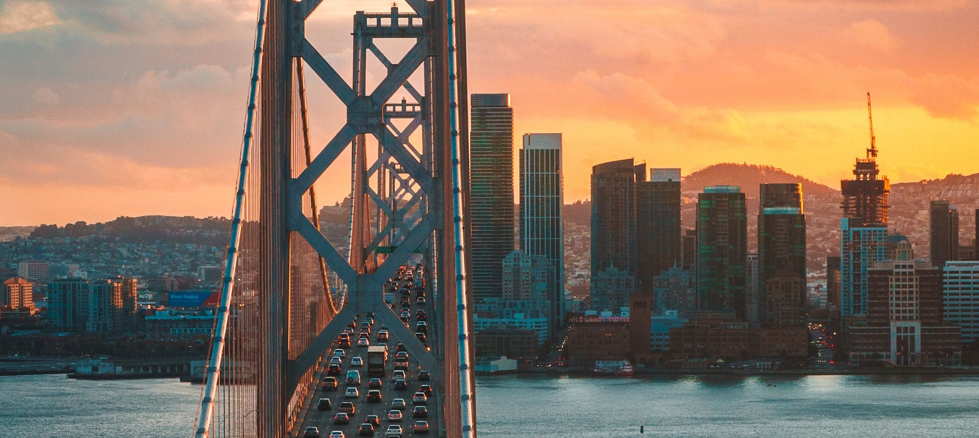 The sun sets in the background behind San Francisco's city skyline while cars travel westward on the upper deck of the Bay Bridge in the foreground.