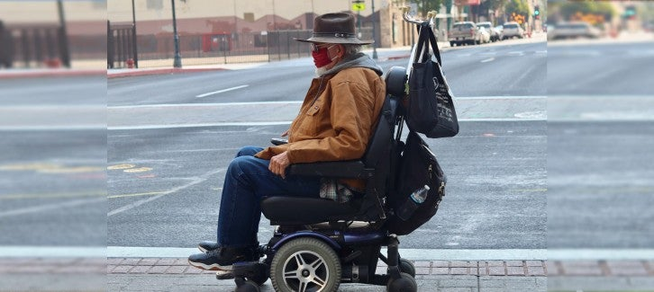 An older man wearing a face mask uses his wheel chair to cross the street.