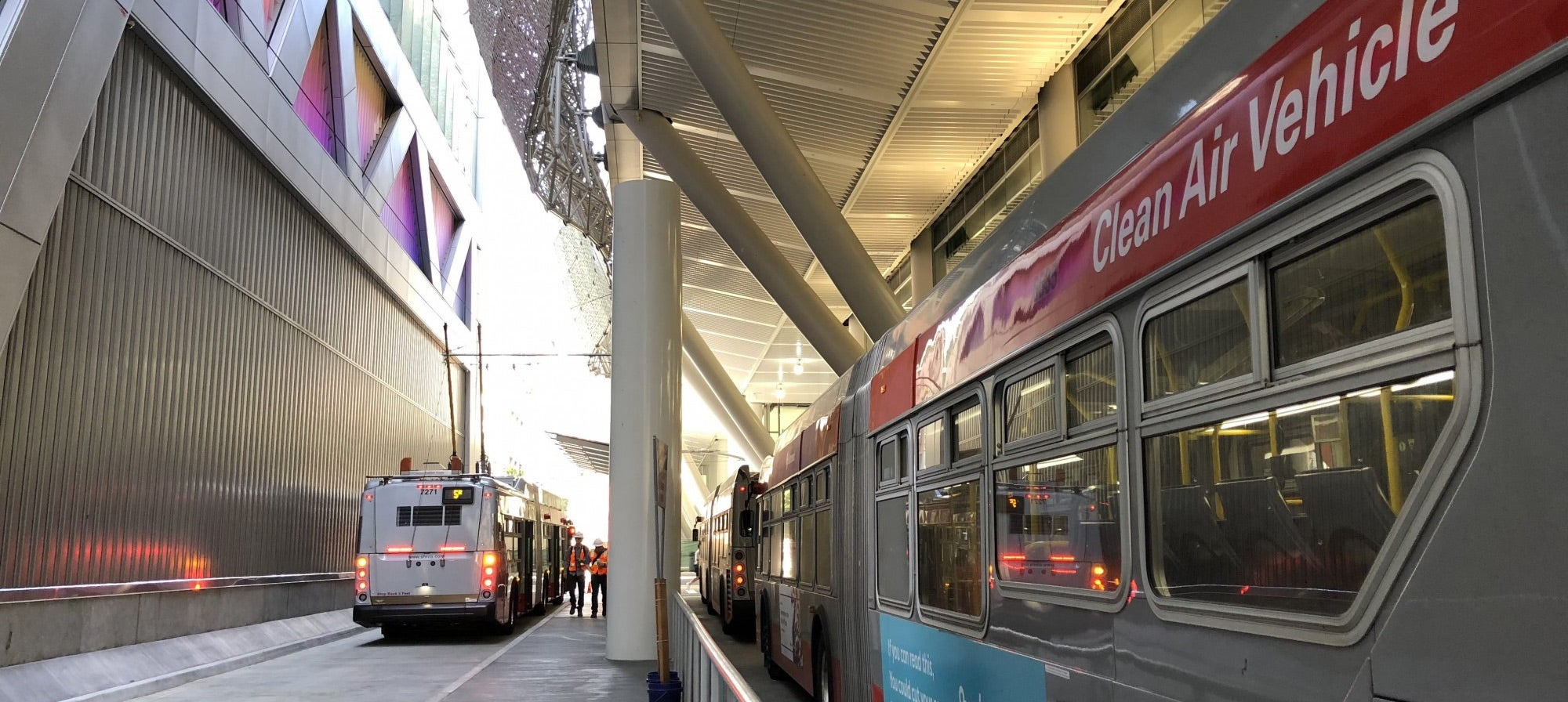 The multi-lane outdoor bus plaza is tucked under the Transit Center's dramatic superstructure.