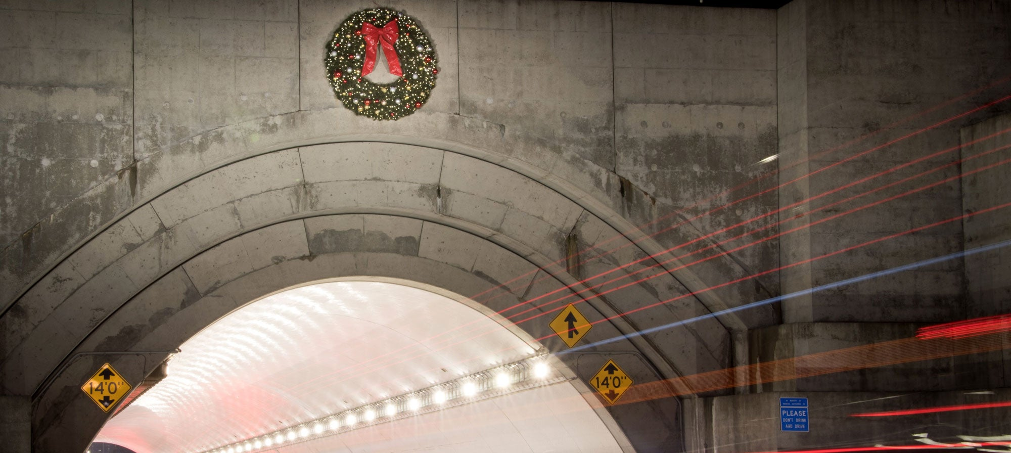 Tail lights streak red as vehicles enter the entrance of westbound Yerba Buena tunnel with the holiday wreath hung above.