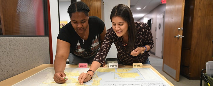 Two high school students place pins on a map at a Plan Bay Area 2040 Youth Outreach event