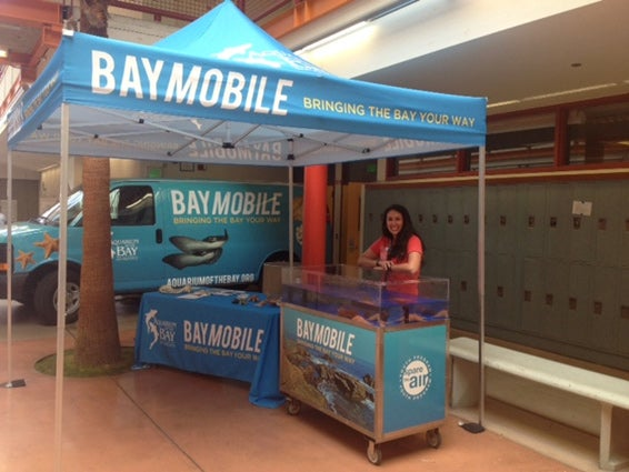 Blair Bazdarich, K-12 outreach coordinator, with the BayMobile touch-tank and van.