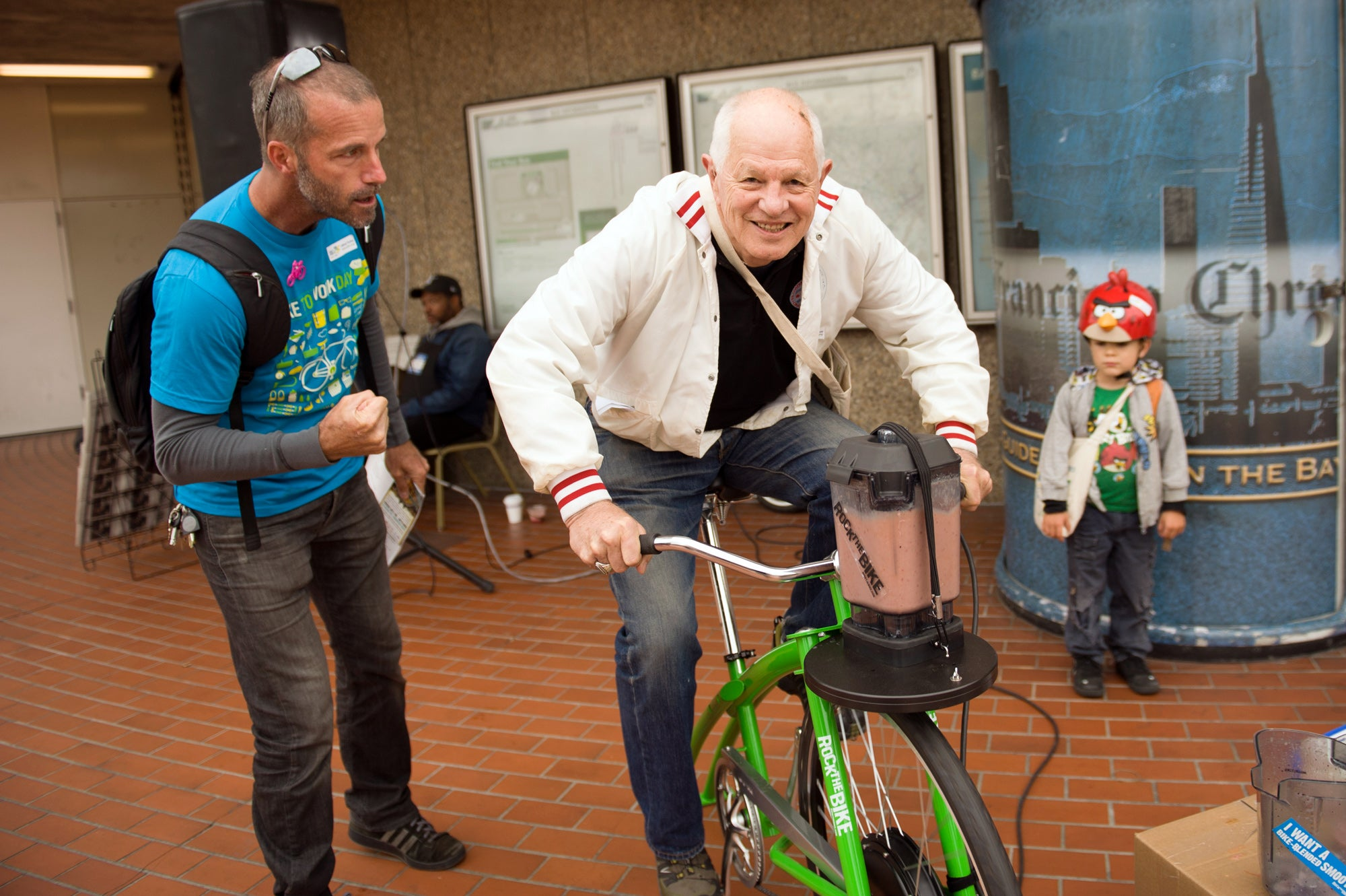 Berkeley Mayor and MTC Commissioner Tom Bates takes a turn at the bicycle-powered smoothie maker at the North Berkeley BART Station.