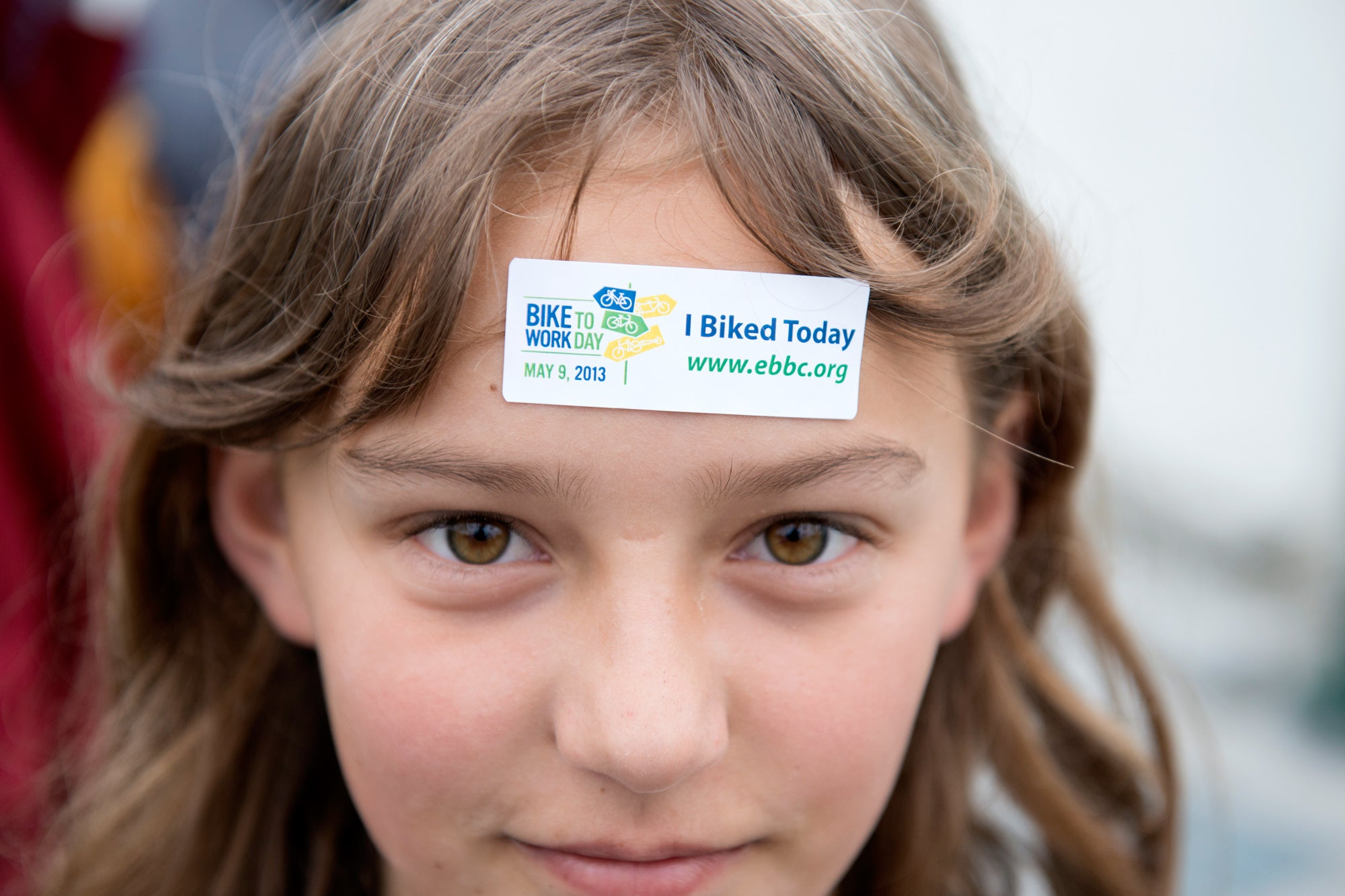 A young girl proudly displays the Bike to Work Day participation sticker at the site of the of a new bike path inaugurated today in Berkeley.