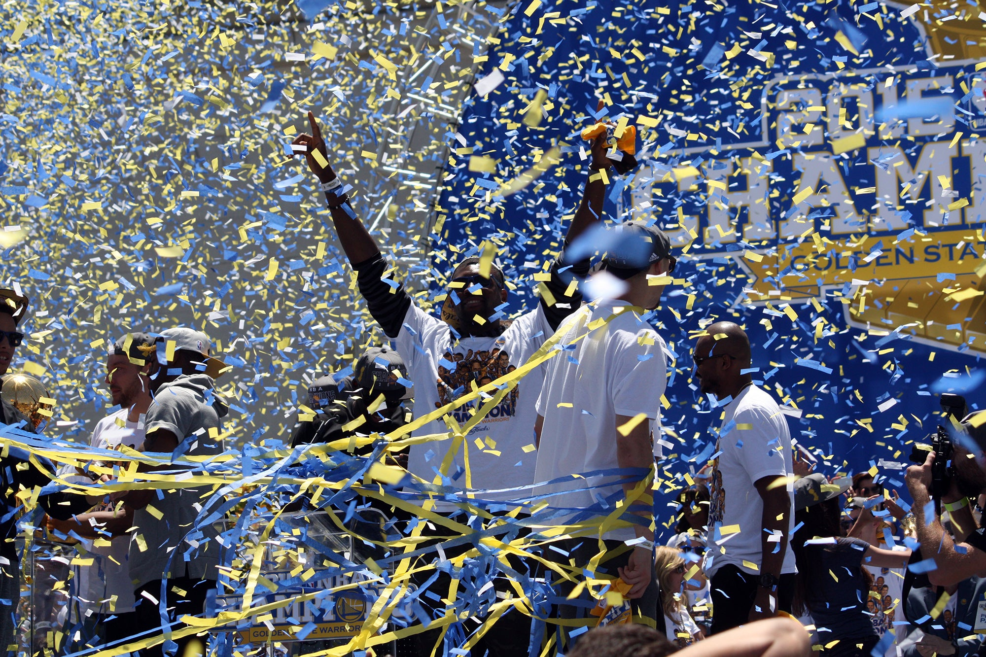 A player emerges from the confetti and streamers, making the V sign with his arms.