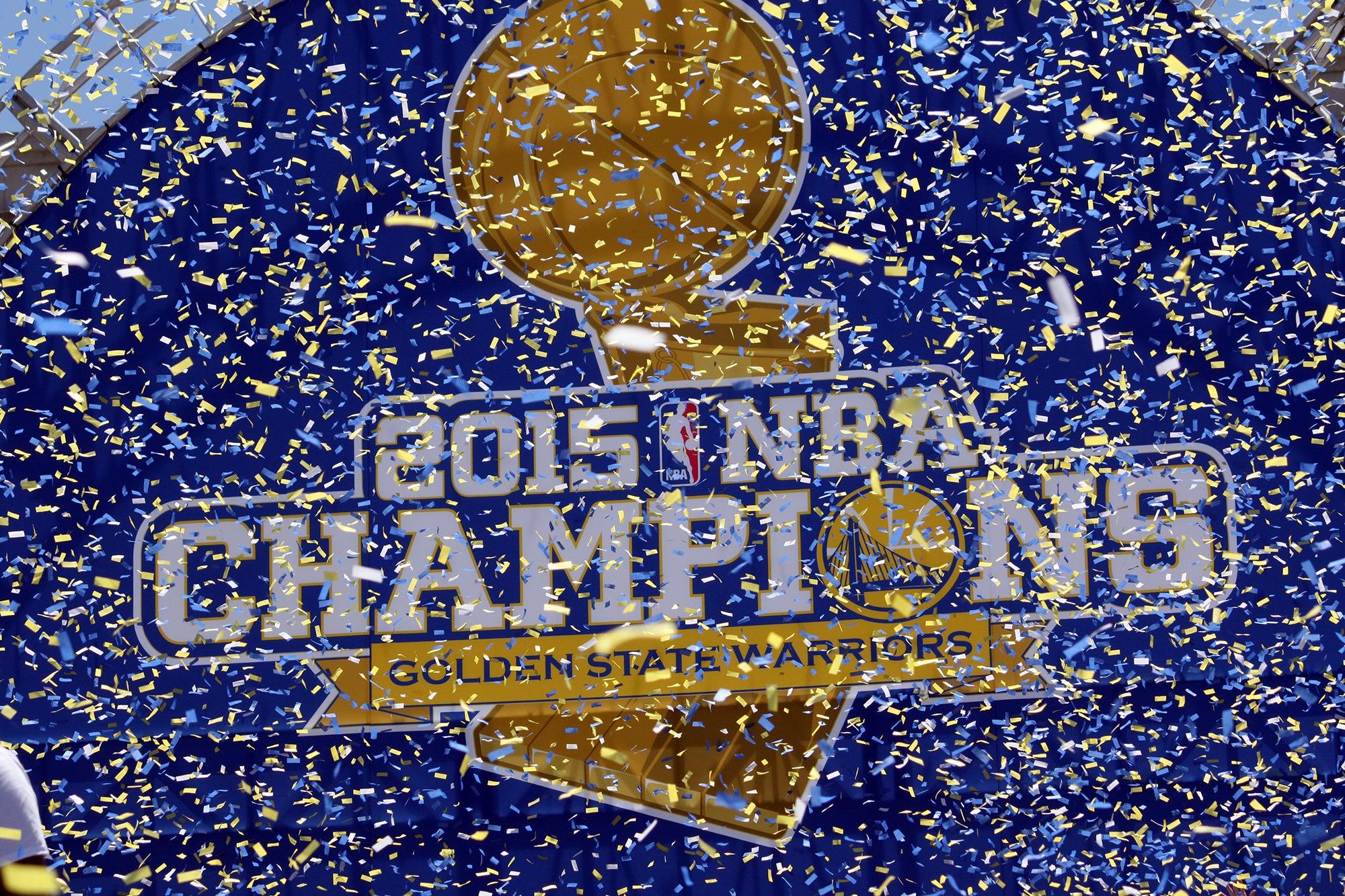 "A backdrop displays the Warriors' new tagline: ""2015 NBA Champions."""