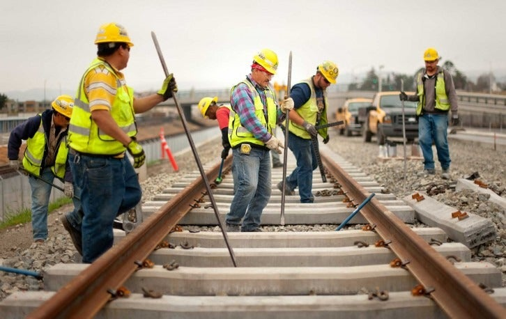 Construction crews do track work near the Washington Road overpass.