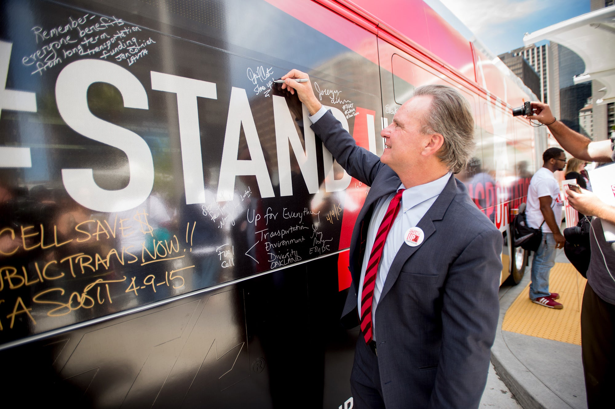 MTC Chair Dave Cortese signing the wrapped VTA bus