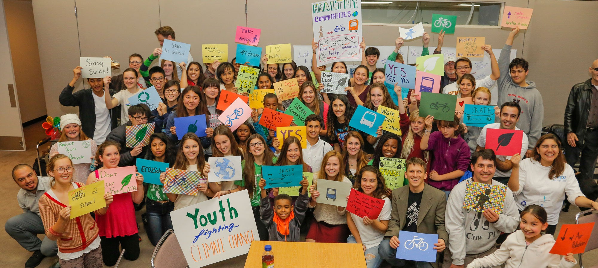 Students gather with signs for a group photo at the 2014 YES Conference